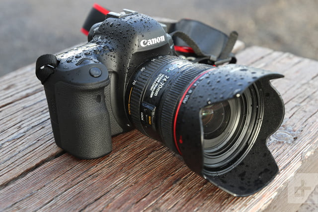 Canon EOS 6D Mark II, covered in droplets, facing diagonal right on wooden table
