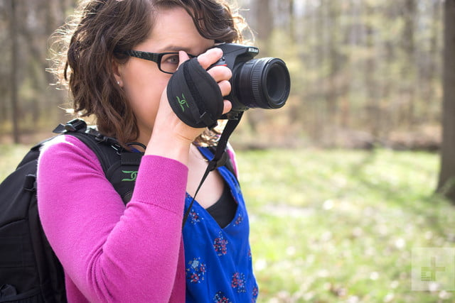 From an angle, the quick release function of the Cotton Carrier StrapShot is demonstrated by a woman holding a camera to her fac