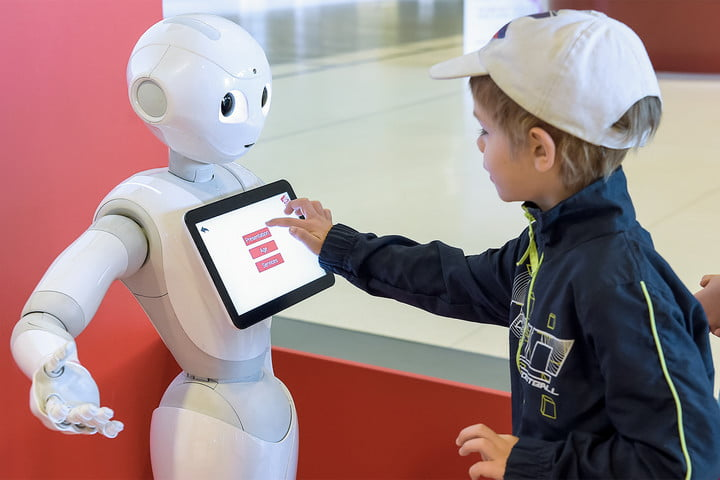 How AI is changing education — A child touches the screen of Pepper the robot