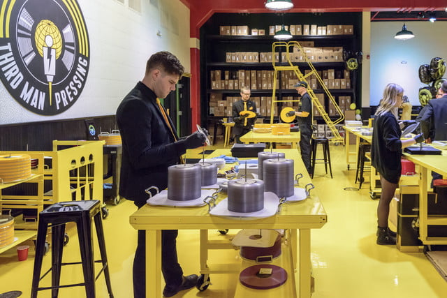 man-placing-records-into-covers-with-stacks-of-vinyl-around